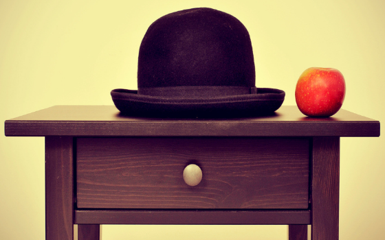 """Picture of a bowler hat and an apple on a bureau, homage to Rene Magritte painting """"The Son of Man"""""""